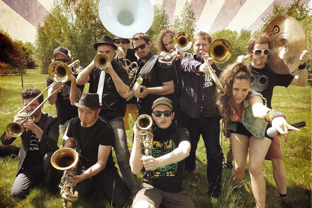 """[fanfare afro punk] Le Wombo Orchestra, c'est un rhum arrangé 18 ans d'âge vieilli en fûts déchainés, distillé à l'école du bitume & de la sueur, c'est une """"rock'o'motive"""" cuivrée, toujours dans le rouge, une armada rutilante de bonobos insolents, tambours battants, menée au chant par Mama J., """"négresse blanche"""" & prêtresse soul imparable …  Portés par les vents de l'Est, forgerons du dance floor, ils enfoncent le clou avec un 8ème opus, """"Roll da Dice"""", ménagerie fracassante, toute de muscles et de ferraille, comme sortie du laboratoire du Professeur Moore. """""""